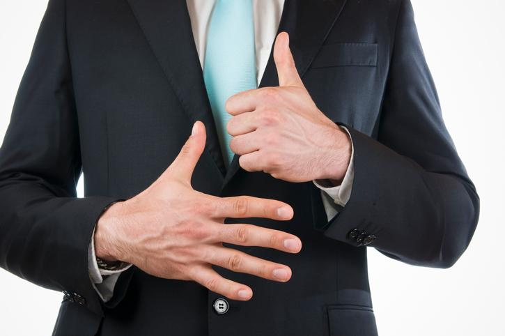 指を6本出す男性
