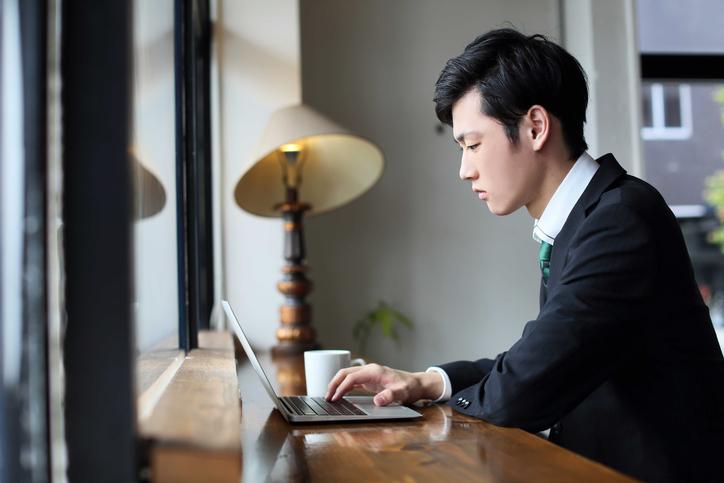 カフェで資料をまとめる男性